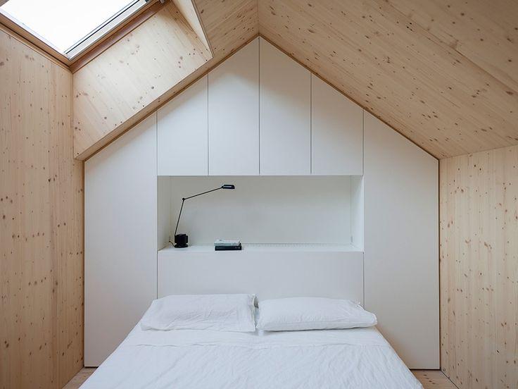 quarto com revestimento em madeira clara e iluminação natural de teto