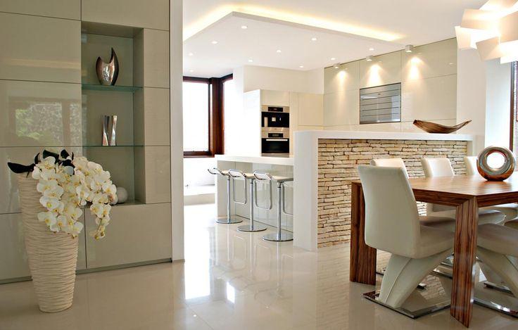 V tejto luxusnej kuchyni je nádherne zobrazené riešenie prepojenia kuchyne, jedálne a obývačky. Kuchynská linka na mieru vo vysokom lesku v odtieni kapučína dokonale harmonizuje s barovým pultom z  Corianu.