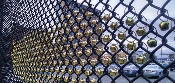 """8,500 bells, each one hanging from a simple jump ring in the openings of the chain link fence, will be installed along A Street in an undulating form. The bells' metallic finish will catch the sun on bright day, and, they will reveal the invisible winds that walk with us on A Street. I believe a simple gesture like these bells becoming part of an everyday object—the fence along A Street—is a way to bring poetry to the everyday."""