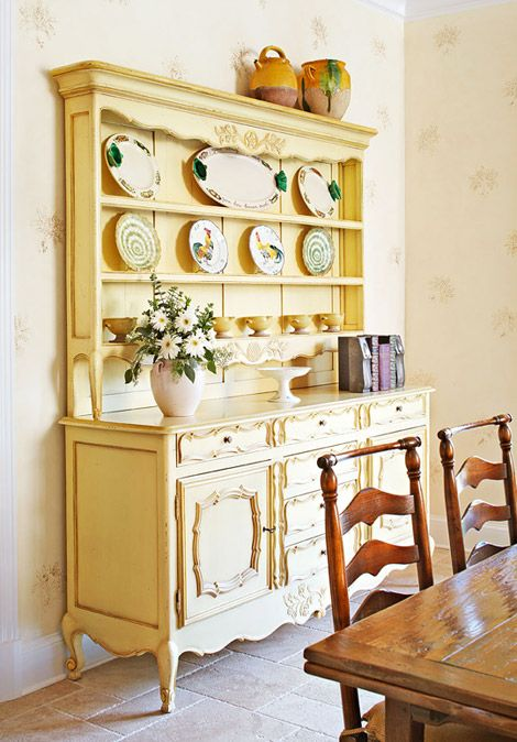 Breakfront displaying collection of rooster-motif and other plates is a reproduction French vaisselier with a yellow-painted finish.
