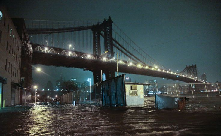 Streets are flooded under the Manhattan Bridge in the Dumbo section of Brooklyn, New York, on October 29, 2012. Sandy continued on its path Monday, as the storm forced the shutdown of mass transit, schools and financial markets, sending coastal residents fleeing, and threatening a dangerous mix of high winds and soaking rain.