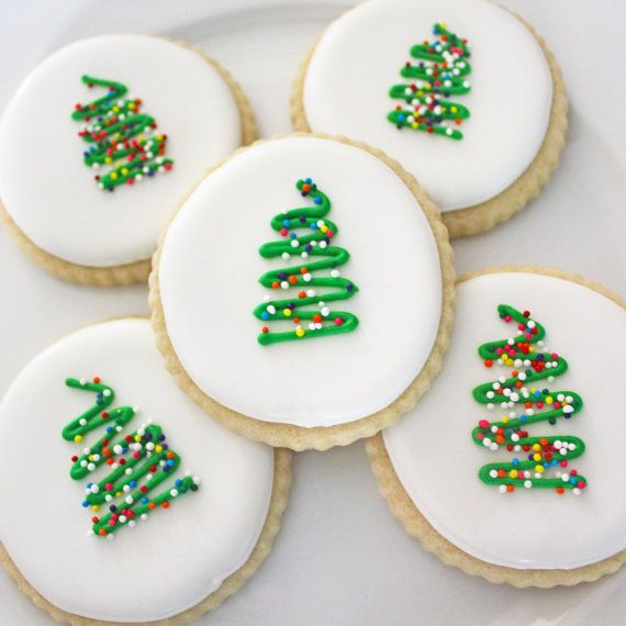Each order contains one dozen Christmas tree sugar cookies! Sprinkles imitate the look of real tree lights and the fluted edges of the cookie compliment the simple style tree. Each cookie is three inches across. This order is ideal of Christmas celebrations and hostess gifts. Each cookie is rolled out thick so that when it arrives on your doorstep it is still perfectly soft! We can personalize your order to make it exactly what youre looking for.  For shipping each cookie is bagged, heat…