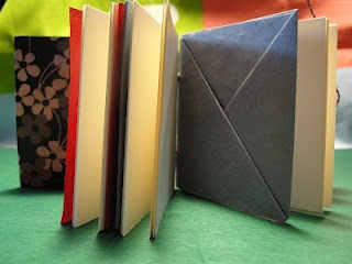 Tiny little square book with origami folded envelopes inside. Closes with a braided string which wraps around a button.