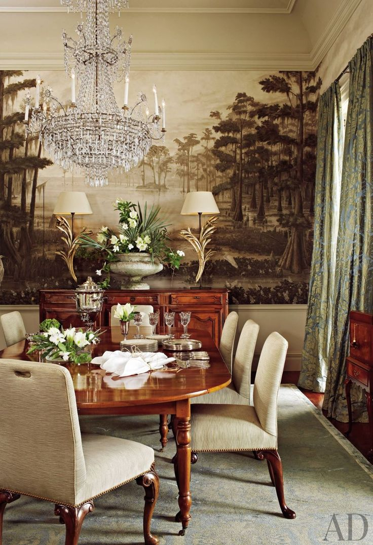 This traditional New Orleasn dining room has a chinoiserie mural of the Louisiana swamp, silk drapes, wooden table and console tables, upholstered white chairs and an ornate chandelier.