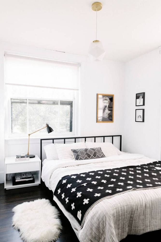 Small monochrome bedroom with a black metal bed frame, simple bedding, a pendant light over the bed, and eclectic art