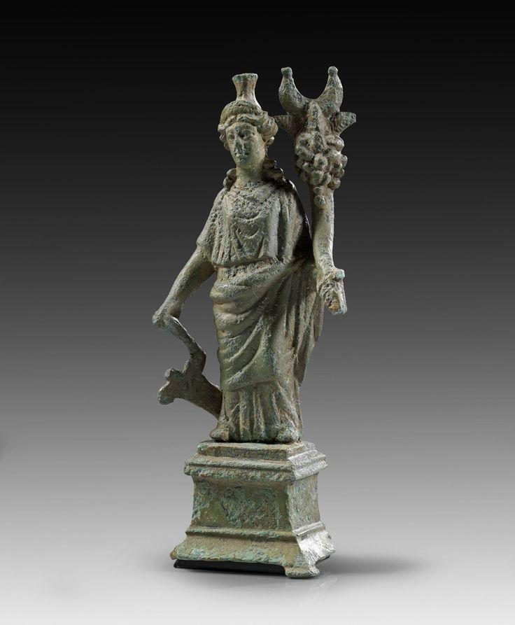 Bronze figure of Fortuna with rudder and cornucopia, with original base. Roman Imperial Period, 1st - 2nd cenury A.D. Bright green patina, tip of the cornucupia broken.