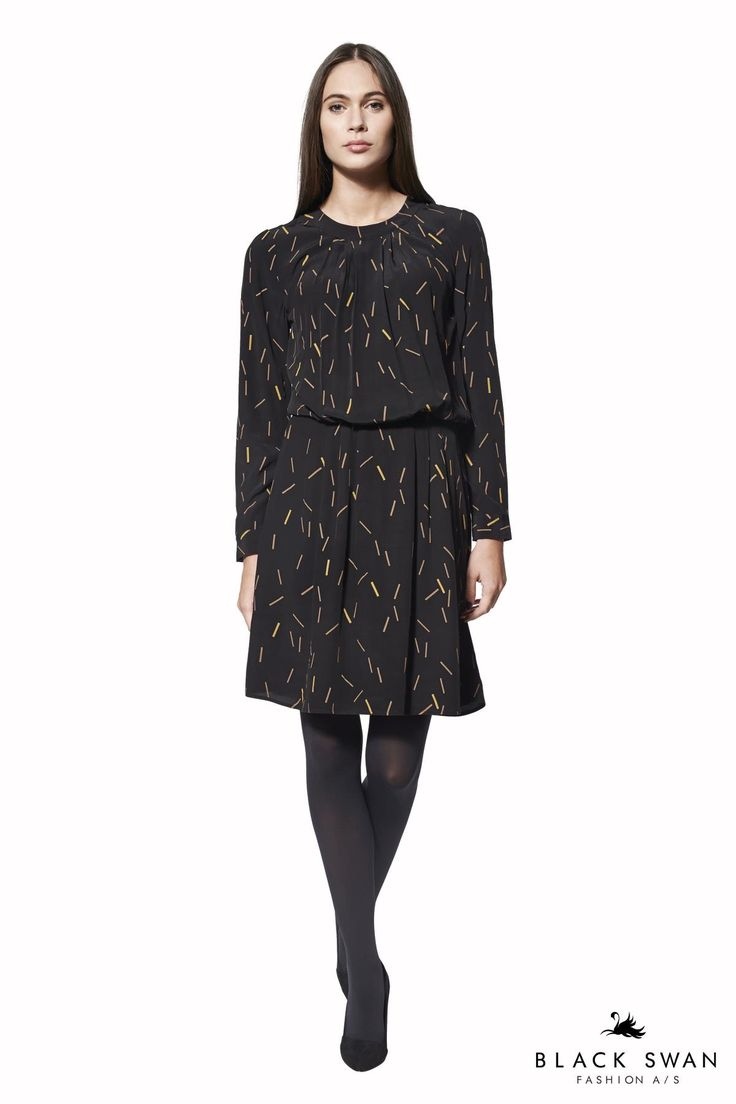 Langærmet kjole med geometrisk print i cognac og karry farver. Den er lukket i nakken med små knapper og slids og har desuden elastik i taljen. Lovely printed dress. Black Swan Fashion