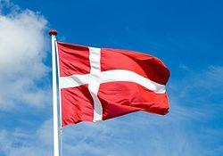 A Danish flag flies from a flagpole against the sky.