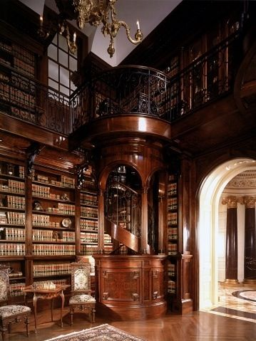 Library with spiral staircase by Harrison Design Associates