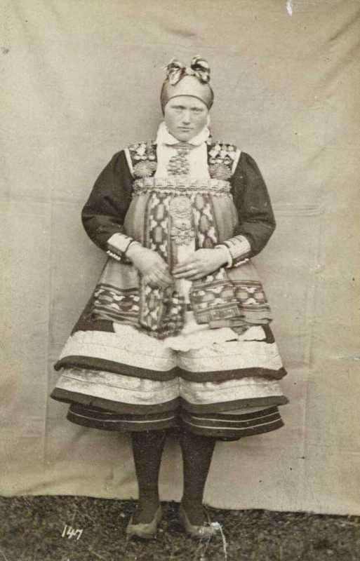 Digitalt Museum - 147. Brudedrakt, Setesdal, Aust-Agder. Fotografert stående utendør mot opphengt bakteppe. Visittkortformat.