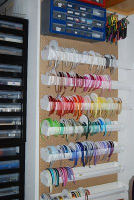 This is a view of my ribbon storage system. This is the system I use for ribbon on spools. These are made of rain gutters that I purchased at Lowe's and had them cut for me. I had them cut in 2 1/2' lengths. They gave me grief about it, but I stood my ground and made them cut it. They thought I was nuts when I told them it was for ribbon storage. The gutters are hung on pegboards