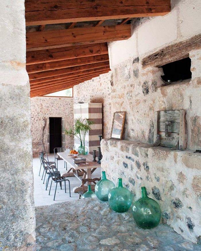 De flessen zorgen voor een kleurrijk accent in deze ruimte met mediterrane uitstraling.