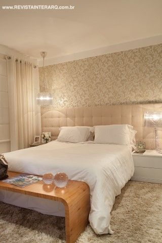 A cabeceira de suede ocupa parte da parede da suíte do casal, revestida com papel de arabescos (Decorações Casarão). As luminárias de acrílico branco fazem contraponto à madeira do banco ao pé da cama.