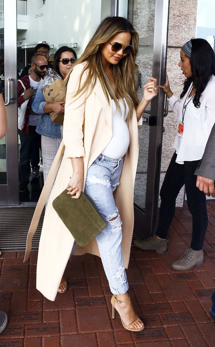 Teigen wore a flowing duster jacket in the faintest shade of peach over a fitted white top and One Teaspoon distressed jeans, plus nude ankle-strap sandals and an olive green suede clutch.
