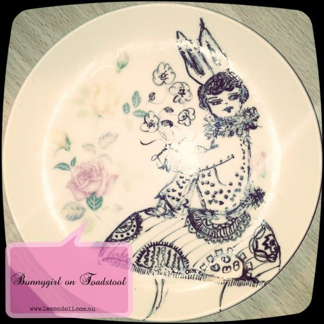 """This is """"Clara"""" the little Bunnygirl posing on her Toadstool. I have used a ceramic ink pen and baked the drawing on the vintage plate for stronger adherence."""