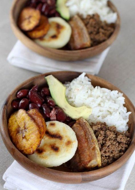 Bandeja paisa - white rice, fried plantain slices, avocado, fried pork belly, and a fried egg