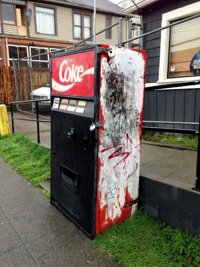 With its sun-bleached buttons and charmingly antiquated Mountain Dew logo, the Mystery Coke Machine has been spitting out sodas on the corner of John and Broadway in Seattle for upwards of 15 years, but no one seems to know exactly for how long—or who re-stocks, maintains, or collects money from the thing. It's as though it fell out of a wormhole and landed free-standing onto this lonely corner.