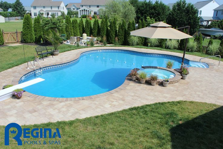 Lagoon-shaped vinyl liner swimming pool with diving board and overflow hot tub located in Sykesville, MD (Carroll County).