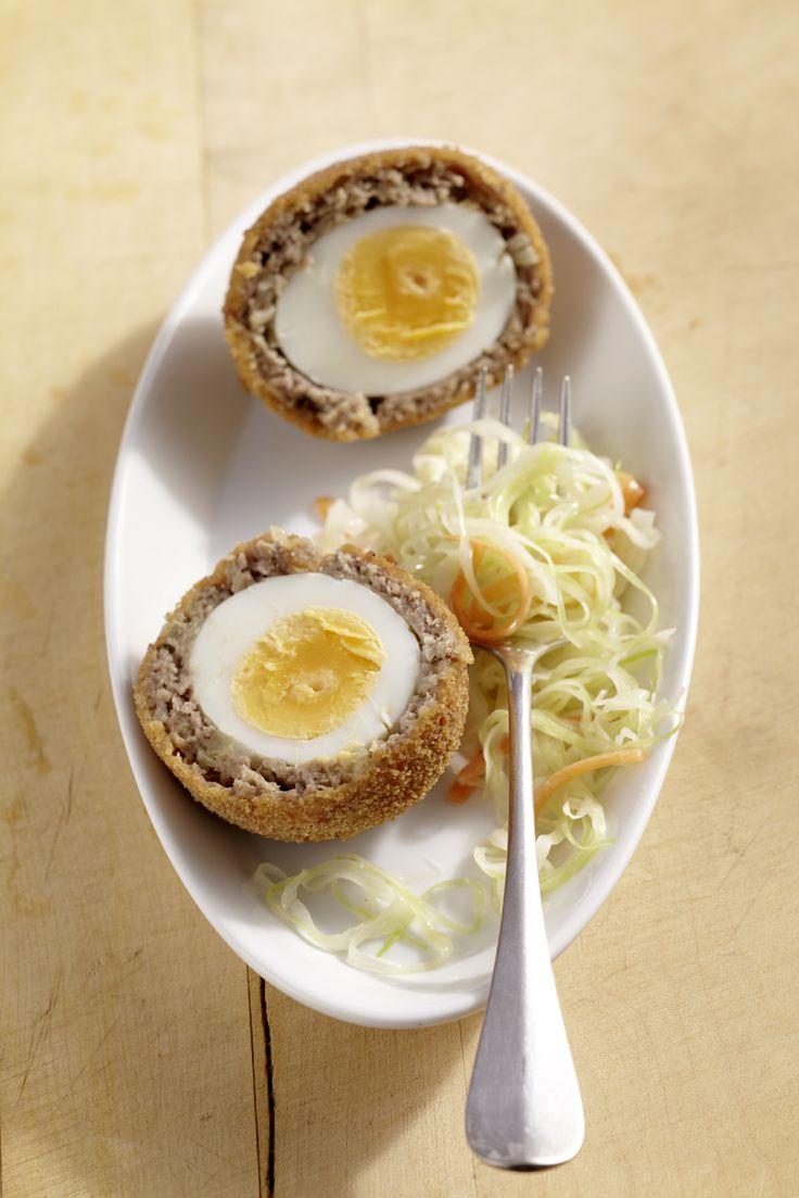 Gekochte Eier umhüllt mit Hackfleisch, paniert und frittiert; serviert mit Krautsalat.