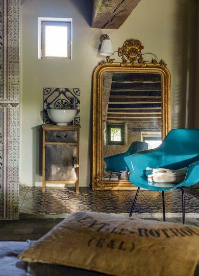 Une partie de la salle de bains a été pensée comme un salon avec son fauteuil moderne coloré et un miroir travaillé doré - Plus de photos sur Côté Maison http://petitlien.fr/79u0