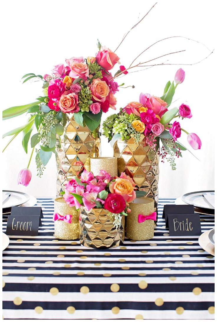 Colorful wedding tabletop decor with black and white striped linen with gold polka dots, bold pink and orange florals in gold vessels and black paper goods with gold calligraphy. Design by I Do! I Do! Wedding Planning, florals by CeCe Designs and Events, paper goods by KW Design, image by Magen Davis Photography.