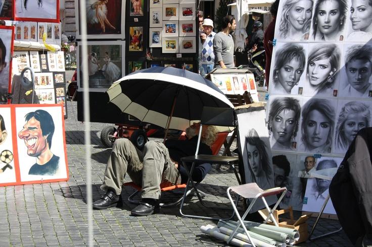 Det er 24 grader varmt, turisterne får tegnet karikatur tegninger under den brændene sol og får kulør - men denne herre under paraplyen og det tykke tøj - hvad laver han ? - Fail det kan vi alle blive enige om :) -Esra