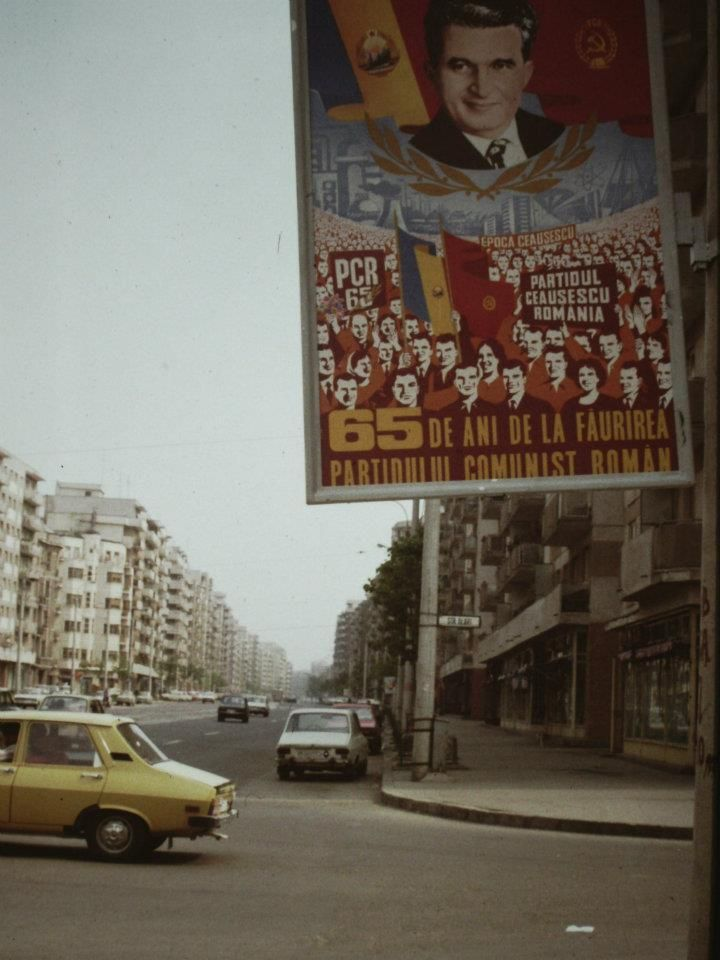 "A propaganda poster on the streets of Bucharest, 1986. The caption reads ""65 years since the creation of the Romanian Communist Party"", while the background states ""Ceaușescu Era"" and ""The Party. Ceaușescu. Romania."""