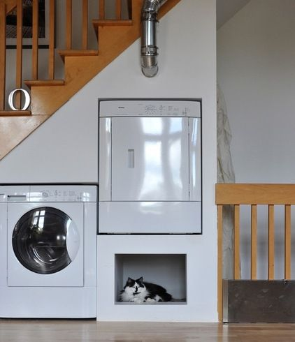 A clever built in under the stairs laundry room - cubby for laundry detergents, bleach... or cats, apparently