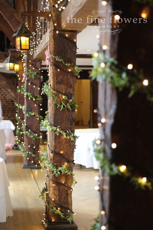 groß  Die Pfeiler auf der Tithe Barn in Great Fosters, geschmückt mit Efeu und Lichterketten. Vom Hochzeitsempfang in Great Fosters