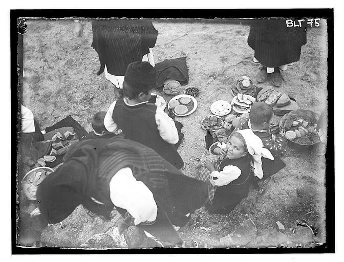 Grèce ; Macédoine ; Negocani (Νίκη-Φλώρινα) (1916-1917) Légende: Jour de fête : femme et enfants autour de plats de nourriture posés sur le sol.  Auteur photoBlanchet, Joseph