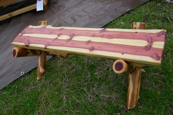"""This adorable bench is made with sawbuck design and from a red cedar log split in half and joined together to make the bench seat. Multiple purposes include a decoration for a country wedding, a child's bench or a plant stand. Measuring 30"""" L x 10"""" H, it is sanded smooth and sealed with polyurethane. One-of-a-kind wood pattern makes this a unique treasure for your home."""