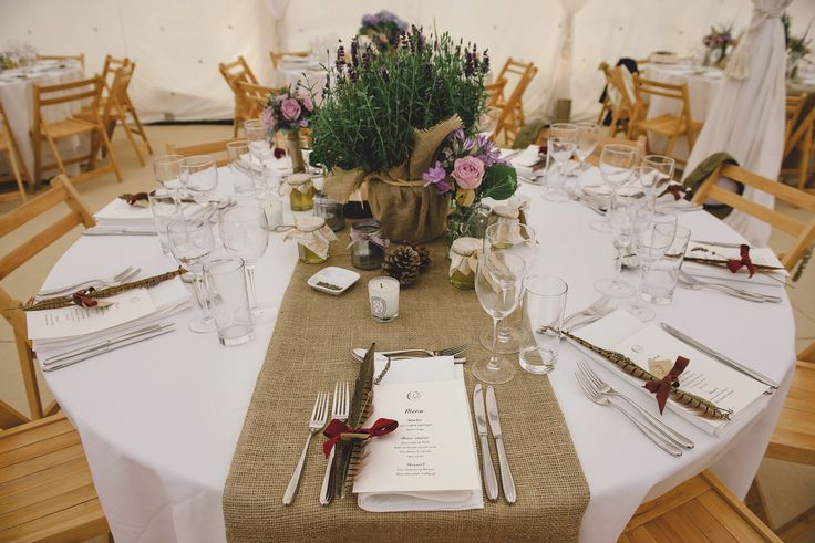 woodland wedding themed table centres with rosemary plants and jam jars with lavender roses, wheat , dried lavender and pheasant feathers