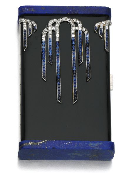 An Art Deco enamel, lapis lazuli, sapphire and diamond vanity case, Janesich, circa 1925. The rectangular case applied with black enamel and cascade motifs set with carré-cut sapphires and diamonds, with lapis lazuli plaque terminals, opening to reveal a mirror, lipstick holder and powder compartment, case measuring approximately 80 x 50 x 15mm, signed Janesich, numbered, French assay marks. #Janesich #ArtDeco #vanity