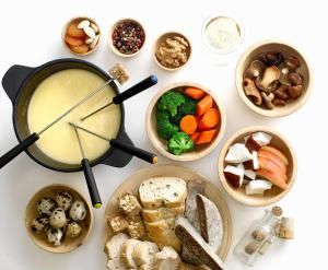 Bowls of cheese fondue with vegetables, mushrooms, bread - Foodcollection RF / Getty Images