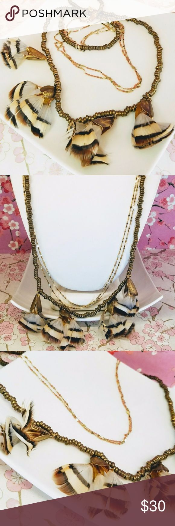 """Anthropologie feather triple gold chain necklace Anthropologie feather triple gold chain necklace. Brass rondelle chain and 2 gold chains. Triple feather in 4 bundles of brown beige tan stripe feathers in a brass leaf. Inner gold chain length is 22"""", outer brass chain 23"""". Feathers are 2"""" long. Great condition. Bohemian chic feel Anthropologie Jewelry Necklaces"""