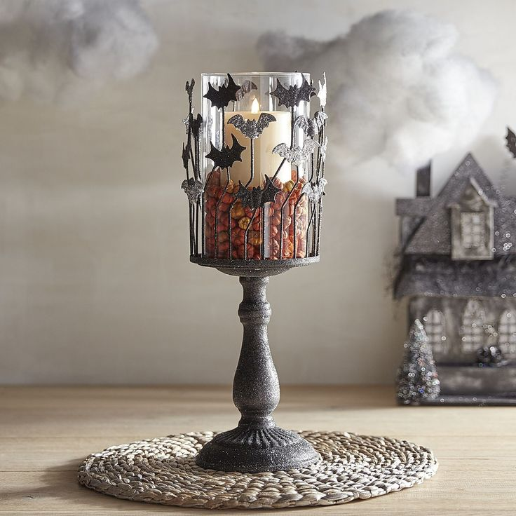 made exclusively for pier our handcrafted wrought iron pedestal hurricane is adorned with bats making their holiday flight add your favorite pillar and