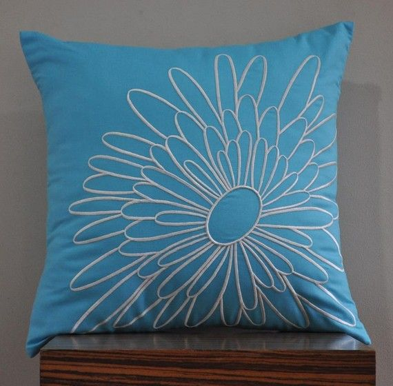 blue with brown flower pillow for the bed. maybe one or to