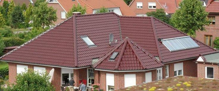 Gründach und Eindeckung mit CREATON Sinfonie Pfanne weinrot glasiert an Haus mit Solaranlage und Terrasse. Dacharbeiten der Ritscher Bedachungen in Hollenstedt (21279) | Dachdecker.com