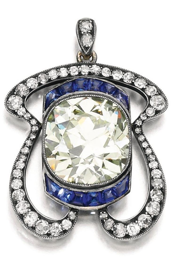 An Art Nouveau sapphire and diamond pendant, early 20th century. Millegrain-set with a cushion-shaped diamond, the frame set with calibré-cut sapphires and circular-cut diamonds. #ArtNouveau #pendant