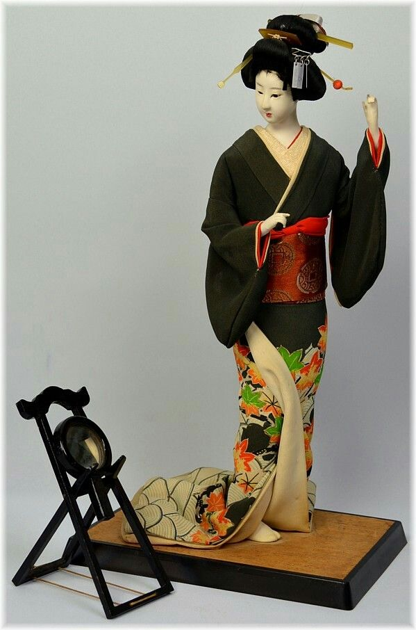 Beautiful Japanese antique doll of a Lady looking in the mirror, 1950's   Japanese antique doll  of a young woman, dressed with hand-painted black silk kimono with autumn leaves motif and silk brocaded obi belt tied on her back. Her hair brused in late Edo style and embellished with comb, long hair pins and silver ribbon . She is fixing her hairstyle looking in the mirror lying on wooden mirror rack.