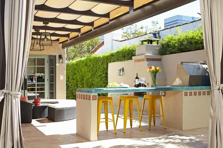 An outdoor cooking station includes extended counter space for friends and family to gather with the cook. The counter is trimmed in the same Spanish-style ceramic tile that adorns the nearby fireplace, creating visual continuity in the patio area.