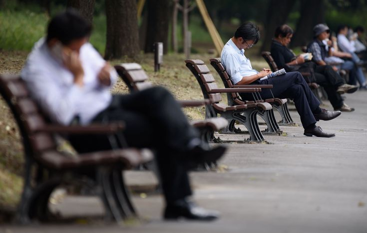Workers rest on park benches in Tokyo in May. Two aides to Prime Minister Shinzo Abe said the nation is planning to bring in more overseas workers to bolster the shrinking labor force.   BLOOMBERG