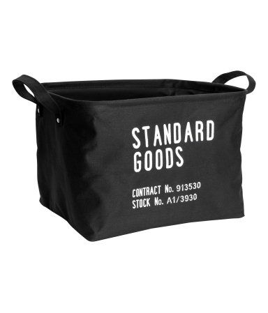 Black. Storage basket in thick cotton fabric with a printed text design. Two handles, concealed metal rim at top for stability, and plastic coating inside.