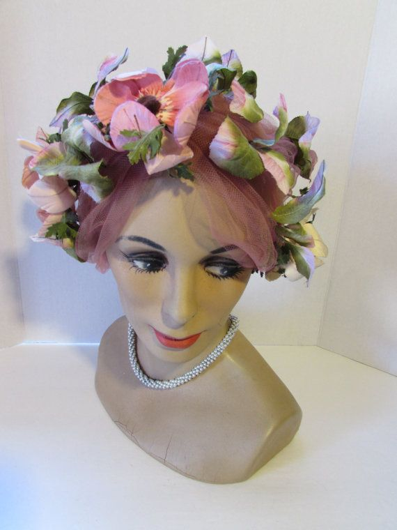 LAST CALL! 40% OFF! Offered is a mid century turban form hat bedecked with a multitude of pink blossoms. This is a wild looking topper--it looks like a mad cap. And, in fact it is--it is a Mad Cap Original. The Mad Cap brand is well-known for creating unusual and whimsical designs. It starts with the turban style form made of a dusty rose net that stretches to encase the head. Attached are 4 wide country roses in pink with pink and green leaves. The leaves are throughout, the roses appear at…