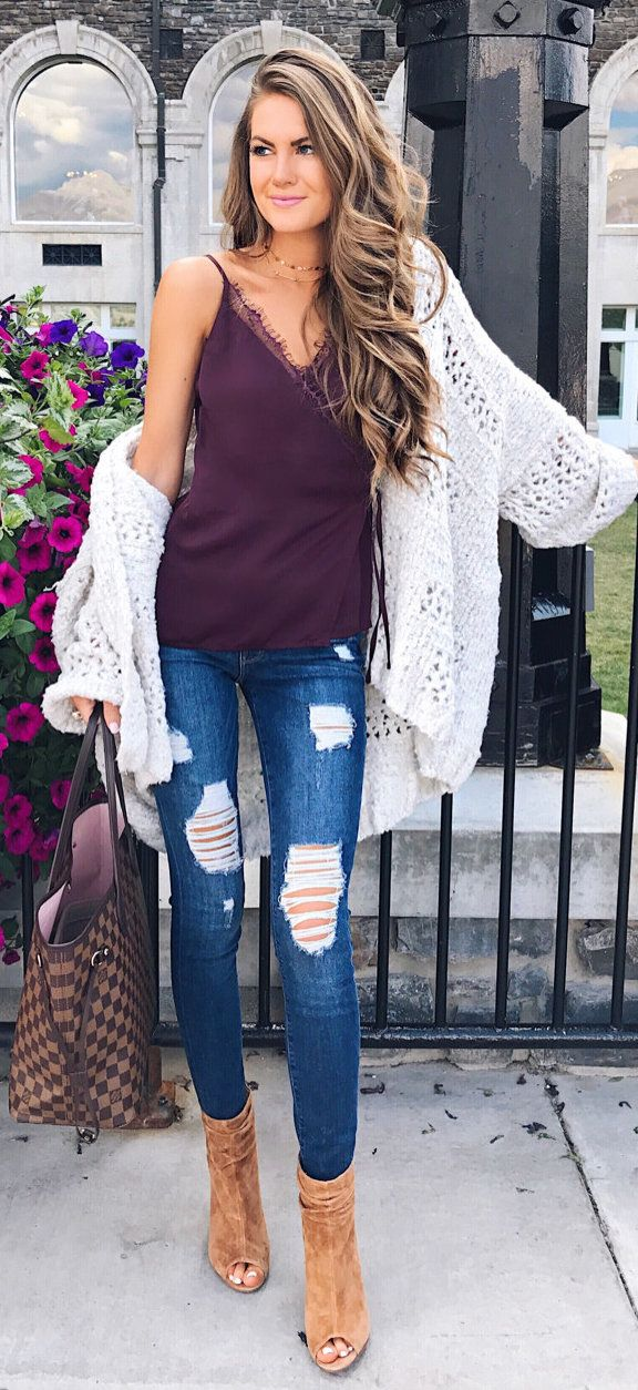 #winter #outfits purple spaghetti strap top, white knit cardigan, and blue faded distressed skinny jeans