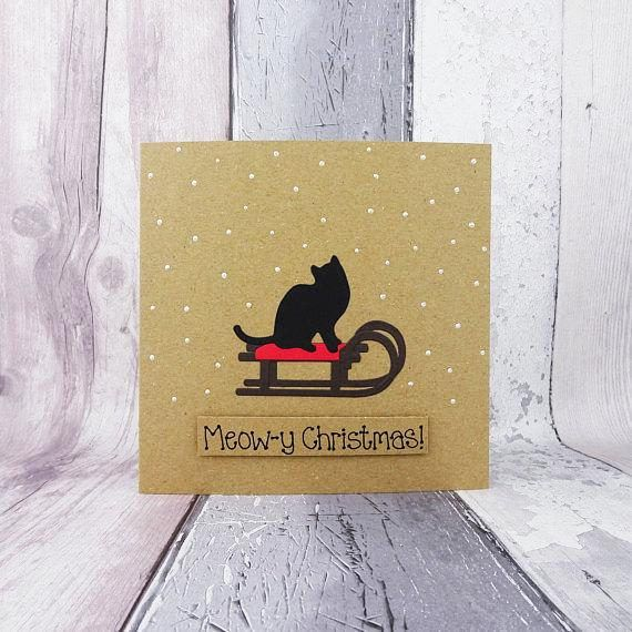 This cat on a sled Christmas card would be perfect for a cat lover, or as a card from the cat. This handmade Christmas card features a black cat on a wooden sled / sleigh surrounded by snow. The sentiment on this handmade pun card is added with 3D foam and reads: Meow-y Christmas! Or