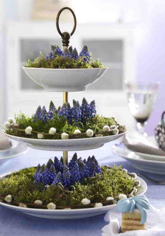 Man hat nie genug Blumenschmuck auf dem Tisch - vor allem beim Osterfrühstück. Damit aber genug Platz für die Leckereien bleibt, kannst du die Blumen doch einfach stapeln! Diese Idee mit zarten Frühlingsblumen auf einer Etagere ist doch klasse, oder?