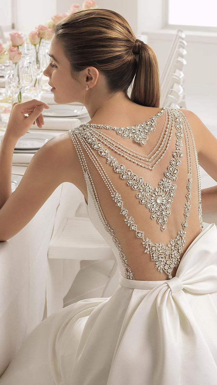 BOMBAY by Aire Barcelona. Timeless with a modern twist, this elegant gown features a dazzling jeweled back and a charming asymmetrical bow. I am obsessed with the back of this dress