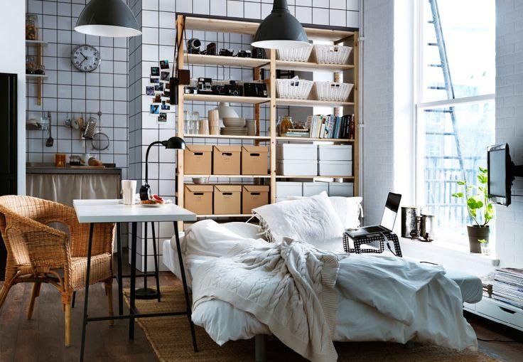 Una camera moderna con un grande letto in primo piano, una parete di piastrelle bianche sullo sfondo e uno scaffale a giorno in legno con tante scatole - IKEA