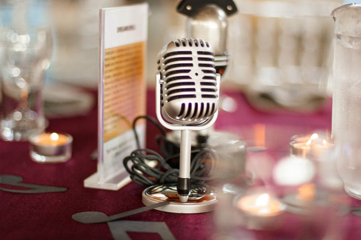 old school mic with different fav. songs printed & displayed on wedding tables as decorations